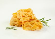 Dried ribbon pasta. Bundles of dried ribbon pasta on white background royalty free stock photos
