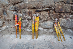 Bundles of incense sticks leaning against a stone wall at a Chinese temple Stock Images