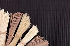 Bundles of raw noodles on black mat background with copy space, top view. Bundles of raw noodles  black mat background with copy space, top view Stock Photography