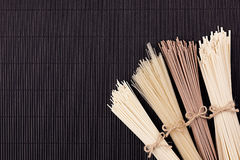 Bundles of raw noodles on black mat background with copy space, top view. Bundles of raw noodles  black mat background with copy space, top view Royalty Free Stock Image