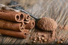 Bundna kanelbruna pinnar för närbild och mald kanel på en sked av kardemummafrö på träbakgrund, makro Royaltyfri Foto