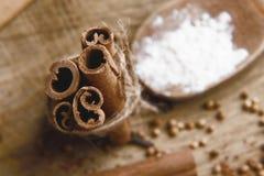 Bundna kanelbruna pinnar för närbild och träsked med vitt mjöl på en sked av kardemummafrö på träbakgrund, makro Fotografering för Bildbyråer
