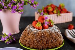 Bundt cake decorated with strawberries and flowers on the background. Pound cake with strawberries and flowers in vase on the background, homemade, babka, fruit royalty free stock image