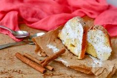 Bundt cake. Sliced Bundt cake and  cinnamon on wooden background Stock Images
