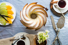 Bundt Cake with Sugar and chocolate glaze on white background. Bundt Cake with Sugar and chocolate Glaze with tea cups and fruits Royalty Free Stock Image