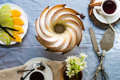 Bundt Cake with Sugar and chocolate glaze on white background. Bundt Cake with Sugar and chocolate Glaze with tea cups and fruits Stock Images