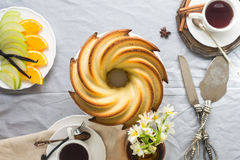 Bundt Cake with Sugar and chocolate glaze on white background. Bundt Cake with Sugar and chocolate Glaze with tea cups and fruits Stock Photo