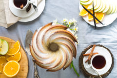 Bundt Cake with Sugar and chocolate glaze on white background. Bundt Cake with Sugar and chocolate Glaze with tea cups and fruits Royalty Free Stock Photography