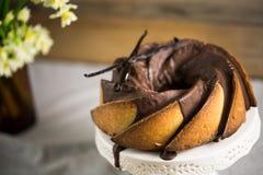 Bundt-Kuchen mit Zucker- und Schokoladenglasur auf weißem Hintergrund Stockbild