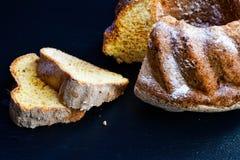 Bundt lemon cake. Slice of moist lemon bundt cake on black slate Royalty Free Stock Photo