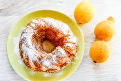 Bundt lemon cake. Slice of moist lemon bundt cake with real lemons Royalty Free Stock Photo