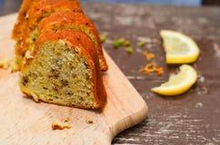 Bundt lemon cake. Slice of moist lemon bundt cake with real lemons in background royalty free stock image