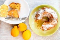 Bundt lemon cake. Slice of moist lemon bundt cake with real lemons on white wooden background Stock Photography