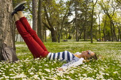 Bunette girl lying in the grass with her legs resting on a tree Royalty Free Stock Photography