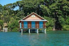 Bungalow över vatten med tropisk vegetation Arkivbild