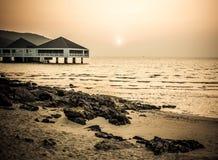 Bungalow dichtbij het overzees met zonsondergang Stock Foto's