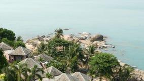 Bungalow e palme sulla spiaggia Tetti dei cottage e delle palme verdi posizionati sulla costa del mare calmo sulla località di so archivi video