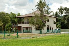 Bungalow House. A luxury modern bungalow house by paddy field in a traditional village atmosphere of Malaysia Stock Photos