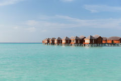 Bungalow huts in sea water on exotic resort beach Stock Image
