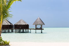Bungalow huts in sea water on exotic resort beach Stock Photos