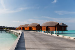 Bungalow huts in sea water on exotic resort beach Royalty Free Stock Photo
