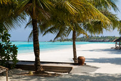 Bungalow huts in sea water on exotic resort beach Royalty Free Stock Photography