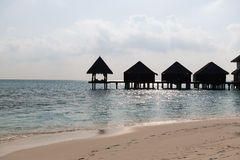 Bungalow huts in sea water on exotic resort beach Royalty Free Stock Photos
