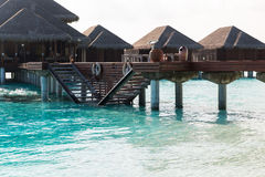 Bungalow huts in sea water on exotic resort beach Royalty Free Stock Image