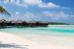Bungalow huts in sea water on exotic resort beach Stock Images