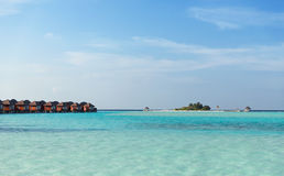 Bungalow huts in sea water on exotic resort beach Royalty Free Stock Images