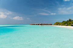 Bungalow huts in sea water on exotic resort beach Stock Photo
