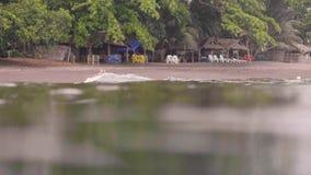 Bungalow met stoelen en chaise zitkamer die zich op leeg strand op overzees bevinden Jonge vrouw die op zandig strand voorbereidi stock videobeelden