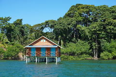Bungalow over the sea with tropical vegetation Royalty Free Stock Images