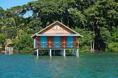 Bungalow over water with tropical vegetation Stock Photography