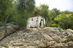Bungalow on a rocky beach. In the bay Stock Photos