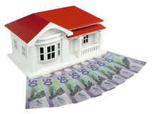 Bungalow villa house model with New Zealand NZ Dollars - side vi. Bungalow villa house model with New Zealand NZ $50 Dollar notes in cash - side view isolated on royalty free stock photo