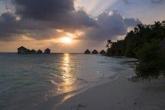Bungalower som förbiser solnedgången, soldagdrivare på stranden arkivfoto