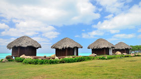 Four bungalows in front of turquoise sea. Stock Image
