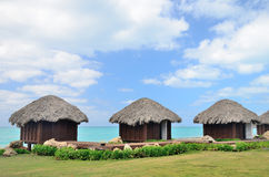 Three bungalows in front of turquoise sea. Royalty Free Stock Photos