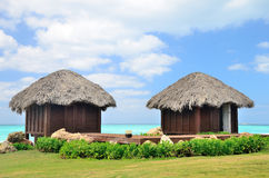 Two bungalows in front of turquoise sea. Royalty Free Stock Images