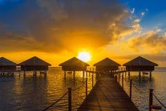 Bungalows no por do sol na lagoa Huahine, Polinésia francesa imagens de stock
