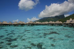 Bungalows Over the Water. A row of Bungalows over the tropical waters of Tahiti Royalty Free Stock Images
