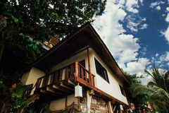 Bungalows among tropical trees. Staircase house on stilts amidst tropical palms Stock Photo