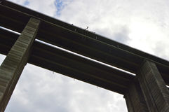 Bungee jump from a high viaduct. Silhouette of bungee jumper in a dark cloudy day jumping from a high viaduct bridge seen from below royalty free stock photography