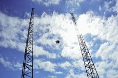 Bungee jumpers. Two silhouetted bungee jumpers from tall cranes with blue sky and cloudscape background Stock Photo