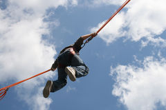 Bungee jumping. Boy on a trampoline in the air with a security line Royalty Free Stock Photography