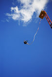 Bungee Jumping from a Crane. Brilliant blue sky in background Royalty Free Stock Photography