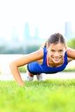 Übungsfrau - drücken Sie ups Training Stockfotografie