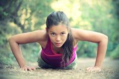 Übungsfrauentraining, das draußen Push-ups tut Stockbild