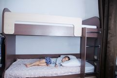 Bunk bed in child room. little girl alone lying on bed. chocolate shade in the interior with white walls. Brown furniture for children domestic room royalty free stock images